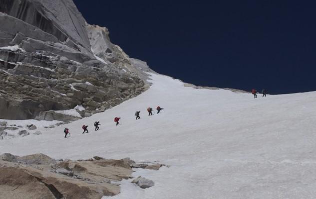 La première pente du glacier est enneigée. Mais nous avons pris la précaution de faire de belles traces bien régulières dans la neige très molle la veille. Les porteurs, juste avec un bâtons filent devant comme des avions !